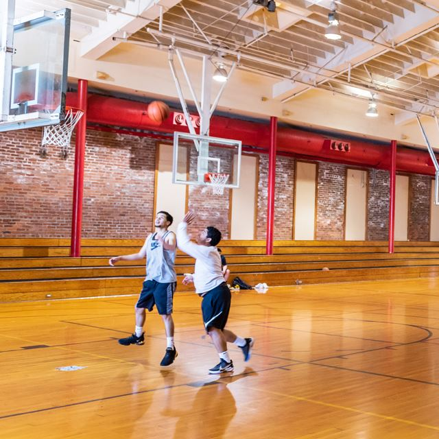 Young men playing basketball in indoor gym