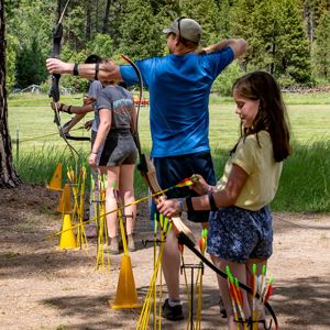Kids and adults at an archery range