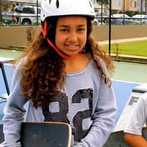 Girl holding her skateboard and wearing a helmet