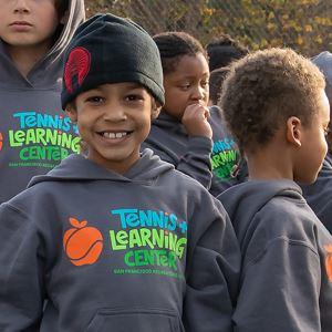 "Group of kids wearing ""Tennis Learning Center"" shirts"