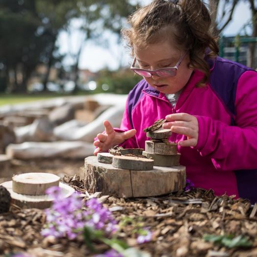 Girl building with rings of wood