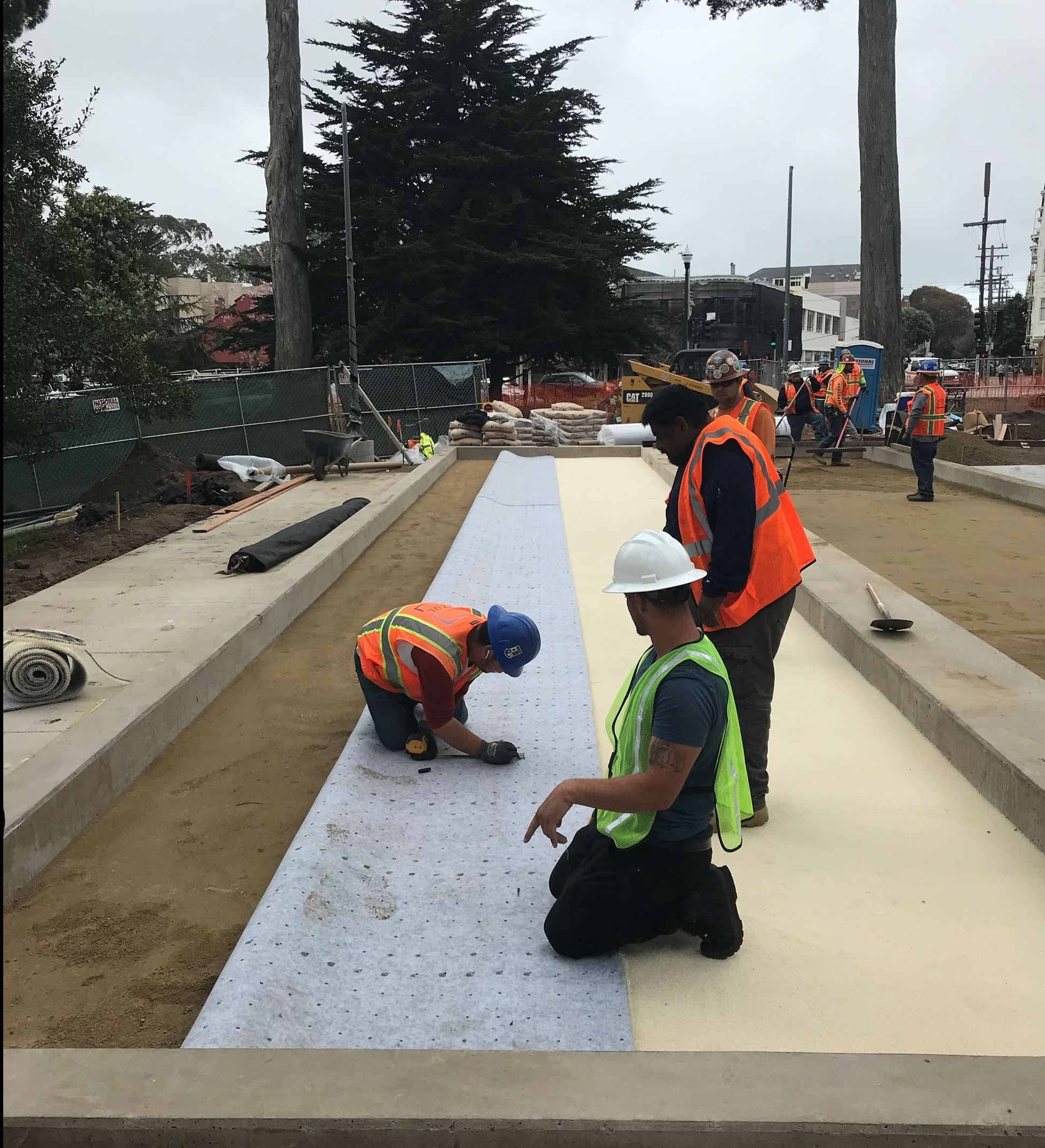 Image shows shows eight construction workers in orange safety vests installing the underlayment for