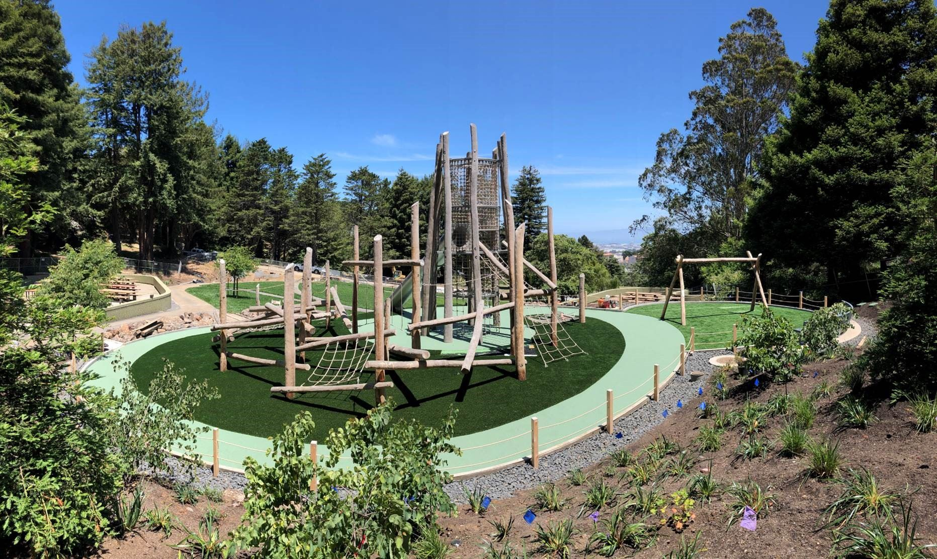 McLaren Park new playground shown with wood log features, a large central wood structure with a slid