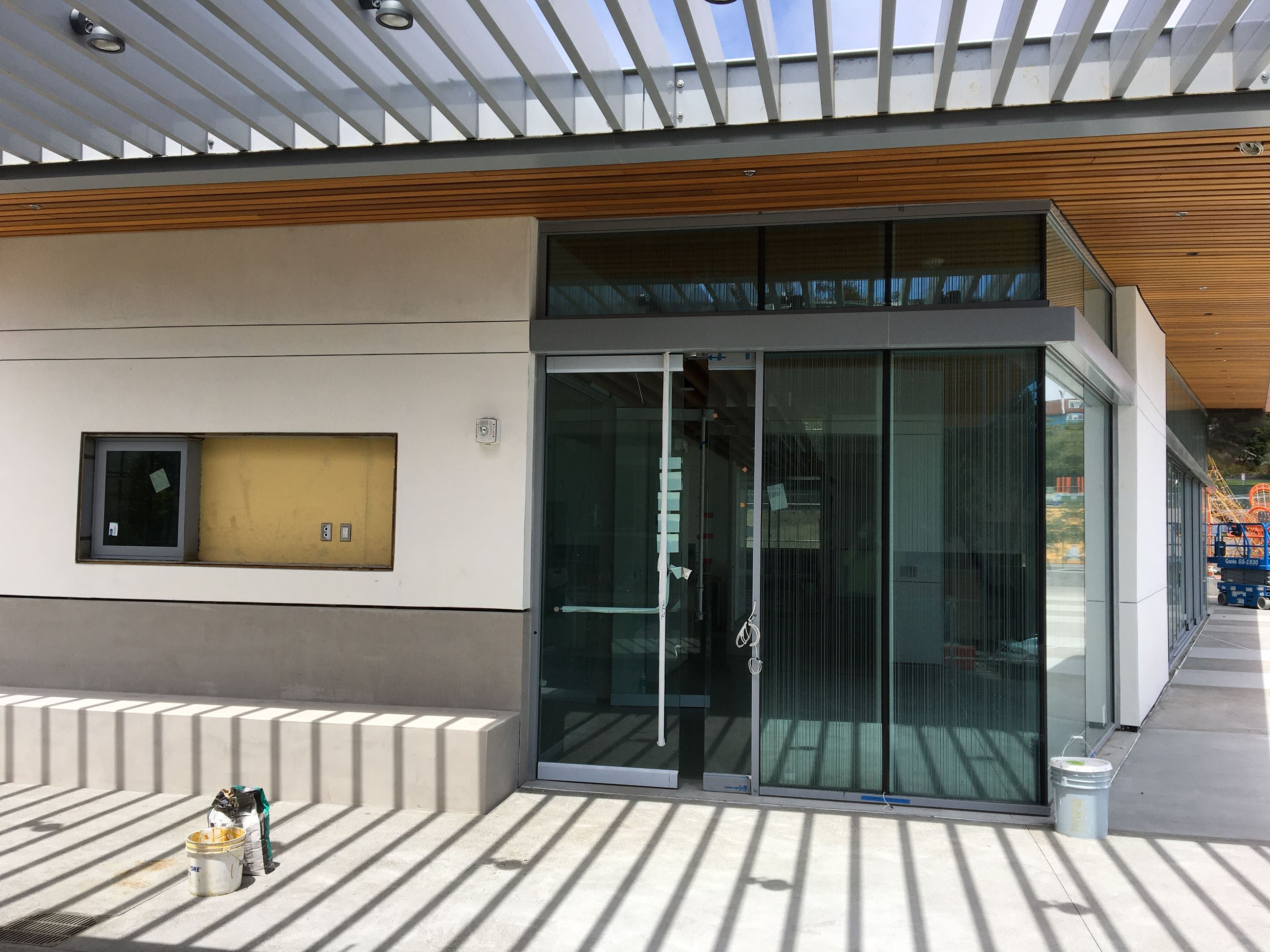 Photo shows exterior of the new clubhouse with glass door and windows, bench seat and slated awning.