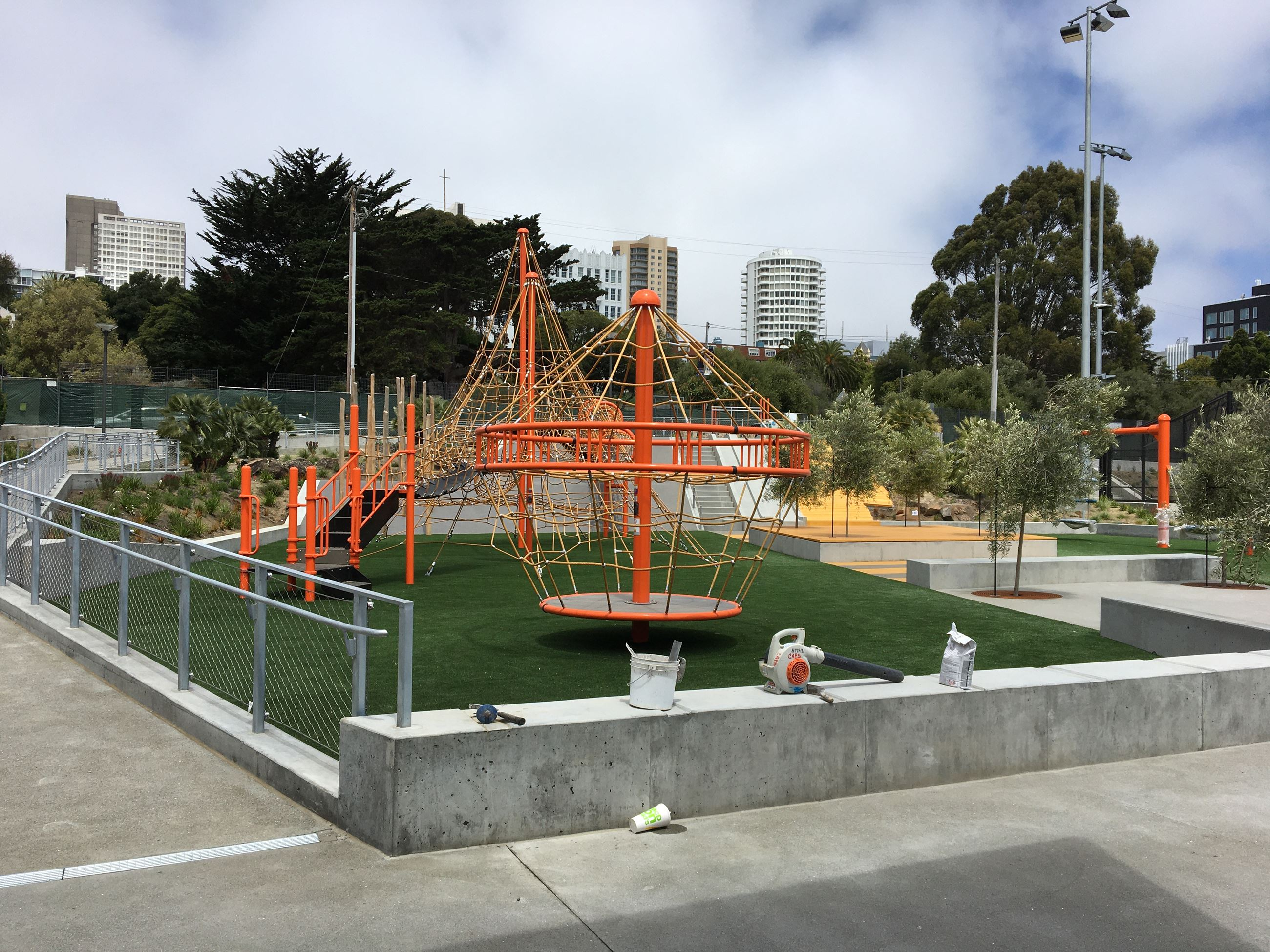 Orange steel pipe and net Playground climbing and spinning bird cage. Bench seating on the left.