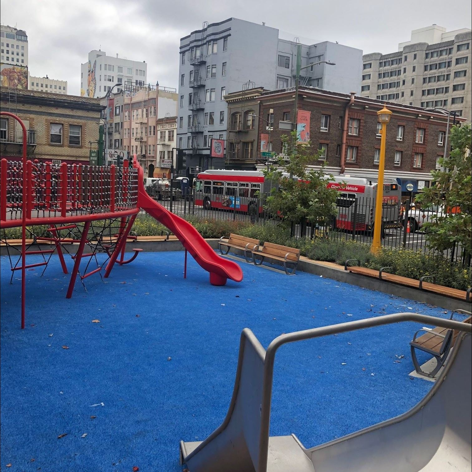View from top of small slide, red play structure blue safety surface. buildings, bus.