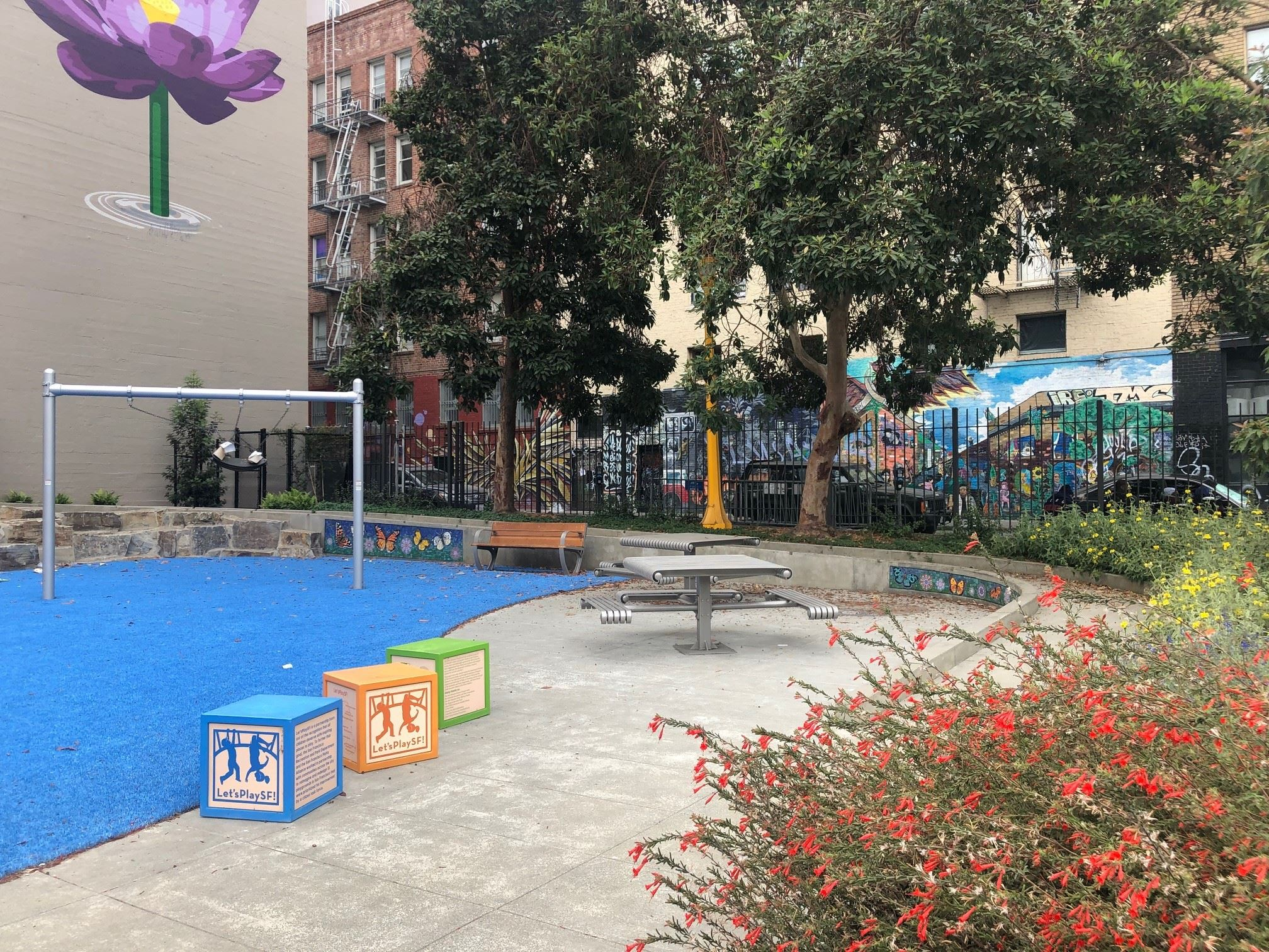 Blue play surface, metal posts with swing, purple flower painted on building, play blocks