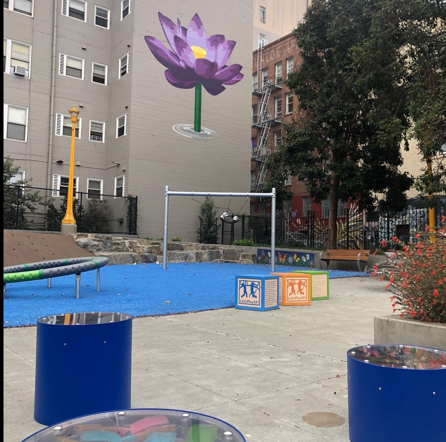 Blue circular light feature, cement, blue safety surface, swings, purple flower painted