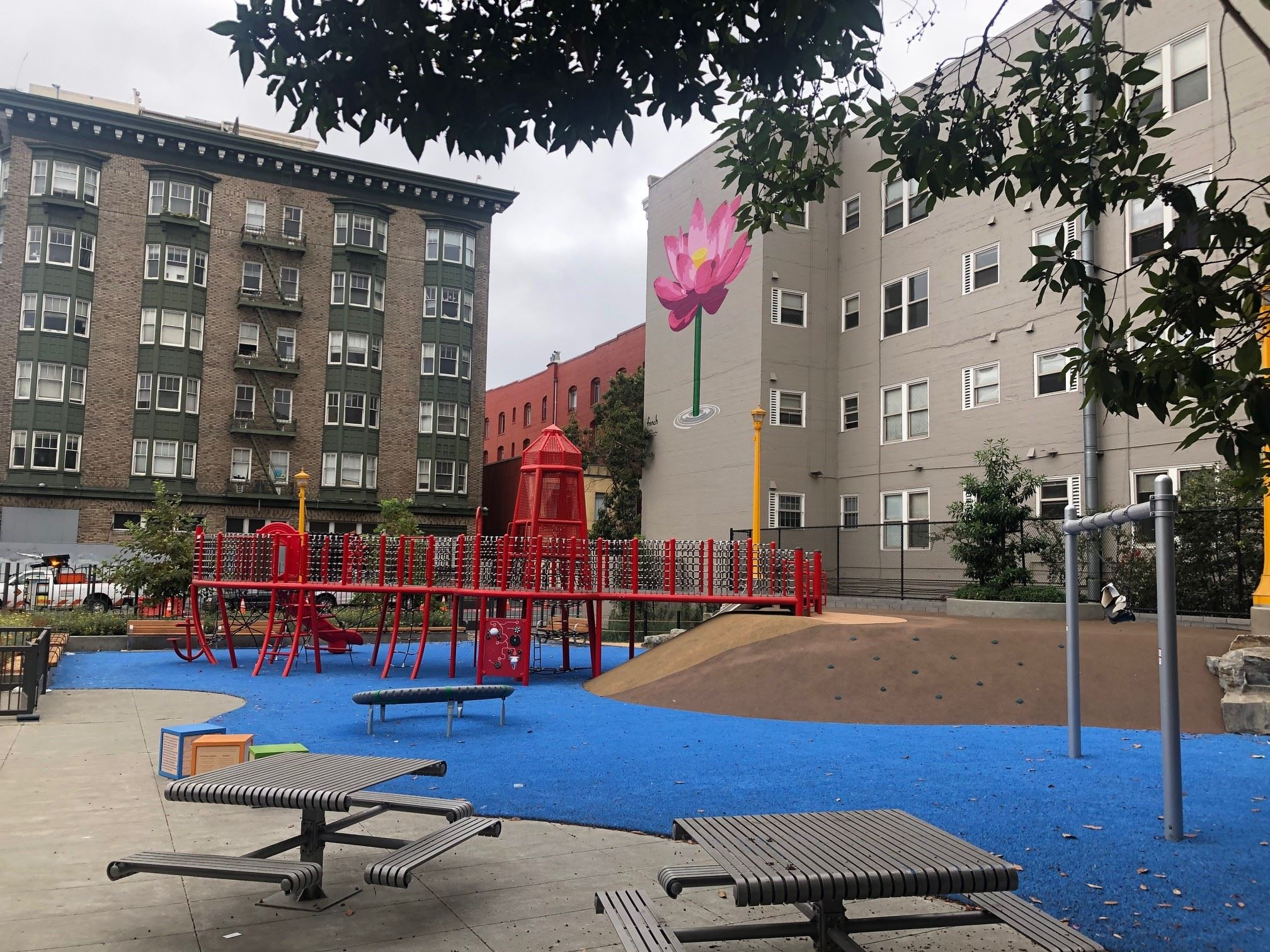 Red play structure, blue play surface, silver metal picnic tables, pink painted flower