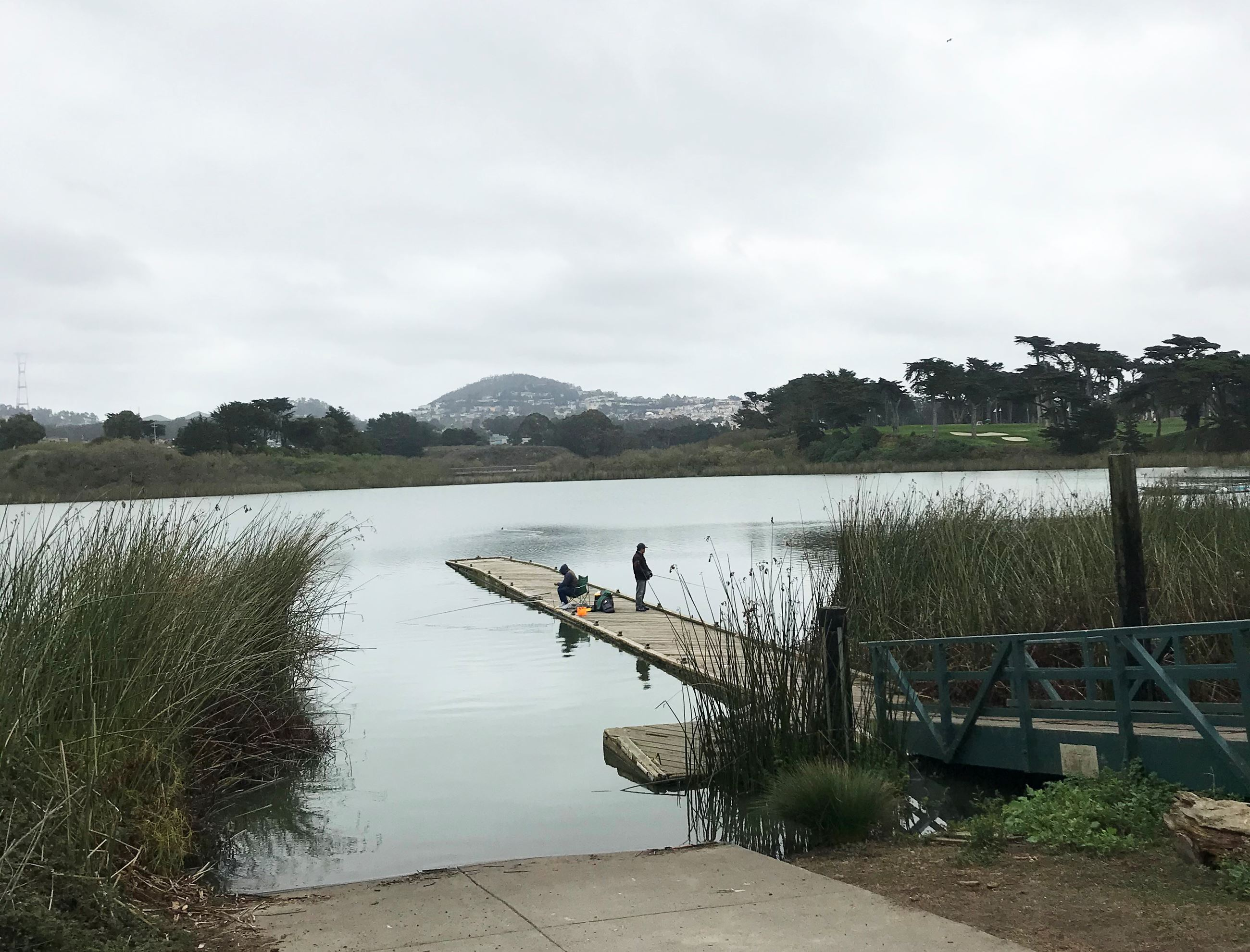 View of Lake Merced Boat Dock with two people fishing on the Lake