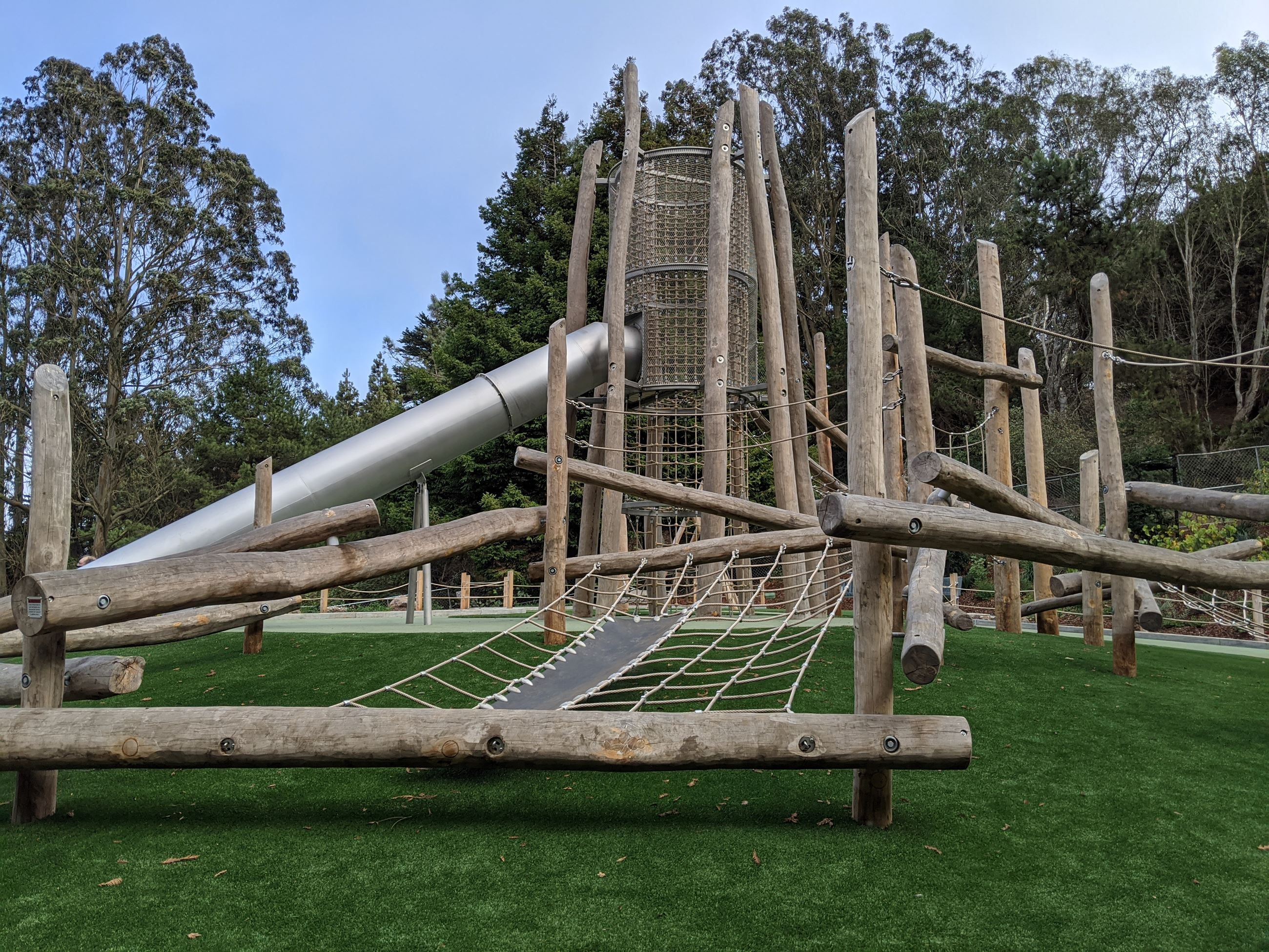 Climbing structure made of logs and rope net with a large tower and slide over green safety surface