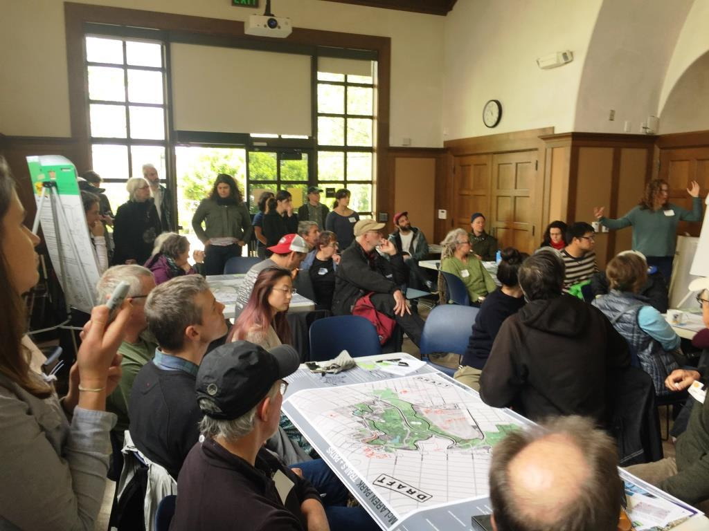 Group of People Sitting at Several Tables with Maps