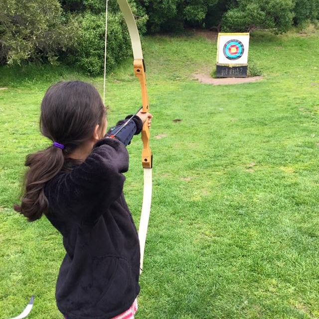 Girl shooting bow and arrow at a target