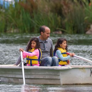 Family rowing a boat on Stow Lake