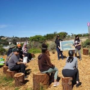 Youth sitting on stumps watching a presentation outdoors